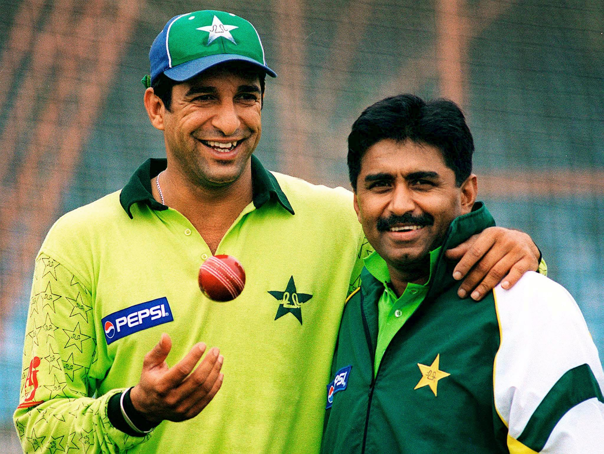 Renowned Pakistani pacer Wasim Akram (L) toss a ball while posing with his team coach and former captain Javed Miandad in the eastern city of Lahore, 26 November 2000. Akram will be the third Pakistani after Miandad and Salim Malik and the 23rd cricketer in the world to cross three-figure mark of Tests in the 2nd Test against England in Faisalabad 29 November. AFP PHOTO/Arif ALI / AFP PHOTO / ALI ARIF